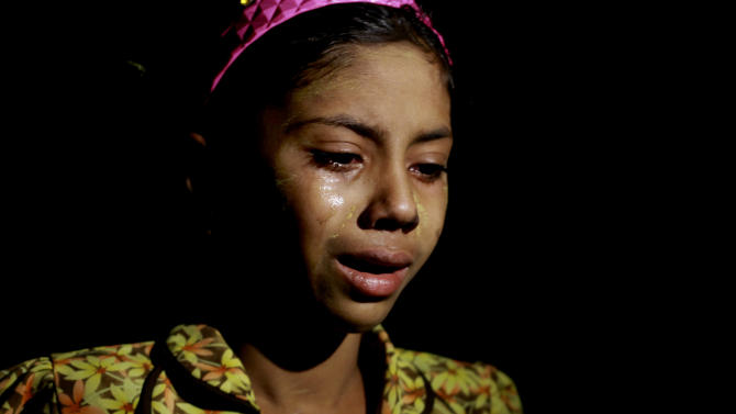 In this April 30, 2013, photo, a Muslim girl weeps as she flees her village, in Okkan, about 70 miles (110 kilometers) north of Yangon, Myanmar. Buddhist mobs hurling bricks overran a pair of mosques and set hundreds of homes ablaze in central Myanmar on Tuesday, injuring at least 10 people in the latest anti-Muslim violence to shake the Southeast Asian nation.(AP Photo/Zin Chit Aung )