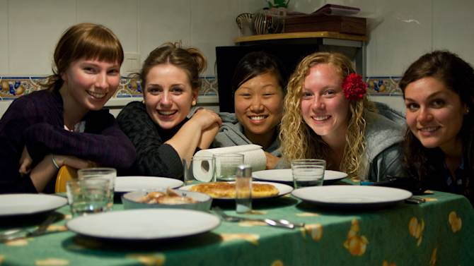 """This March 7, 2010 photo provided by Lauren Hook shows her, left, a new Spanish friend, Carmen Lleo Badal, and other U.S. students Grace Choi, Leah Kosmoski, and Laura Grace Janeskiss before eating a traditional Spanish tortilla omelet at Lleo Badal's family home in Castellon, Spain during the Magdalena Festival. After decades of laissez-faire and faith that just breathing the air in foreign lands broadens horizons, American colleges and international programs are pressing students harder to get out of their comfort zones. """"I noticed a lot of these kids, first time out of the country, all they wanted to do was party,"""" said Hook, a University of Georgia senior who spent the spring of 2010 in Spain. The embarrassing sight of fellow Georgia students stumbling drunkenly around Valencia belting out Bulldog fight songs pushed her to explore more on her own. She also appreciated program activities setting up meetings between American students and locals. Meeting a Spanish boyfriend also helped. (AP Photo)"""