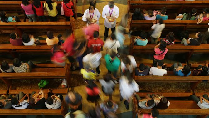Filipino Catholics receive communion during a mass at the Shrine of Our Lady of Perpetual Help in suburban Paranaque, south of Manila, Philippines on Sunday March 3, 2013. Filipinos in Asia's largest predominantly Roman Catholic nation on Sunday went to church that awkwardly had no pope for the first time in 600 years and prayed for the smooth rise of a successor to Benedict XVI who can lead an embattled church. (AP Photo/Aaron Favila)