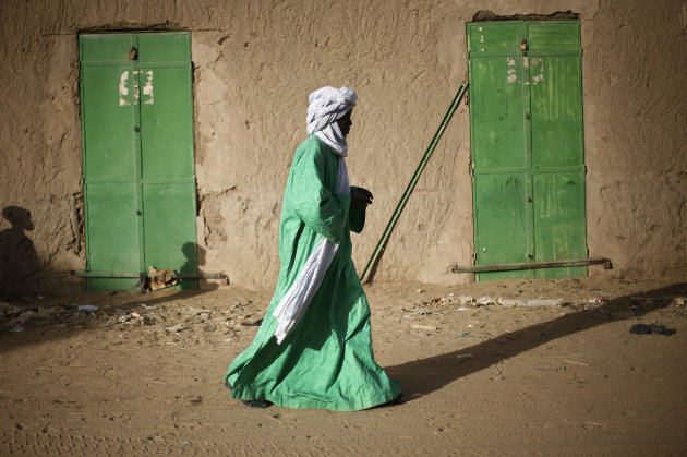 A Malian man dressed in green walks between green doors of closed shops in Gao, northern Mali, Tuesday Feb. 5, 2013.  Troops from France and Chad moved into Kidal in an effort to secure the strategic