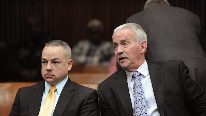 From left, Joseph Weekley and his attorney Steve Fishman sit at Frank Murphy Hall of Justice in Detroit on Friday, Jan. 30, 2015.  At the prosecutor's request, a judge dismissed the last charge against Weekley, a Detroit police officer who fatally shot a 7-year-old girl during a raid.  Two trials against  Weekley ended without verdicts on a charge of reckless use of a gun.   Weekley shot Aiyana Stanley-Jones as she slept on a couch in a Detroit home in 2010. It occurred during a frenzied raid by elite officers who burst through the door to search for a murder suspect after throwing a flash grenade to confuse anyone inside. (AP Photo/Detroit News, David Coates)  DETROIT FREE PRESS OUT; HUFFINGTON POST OUT