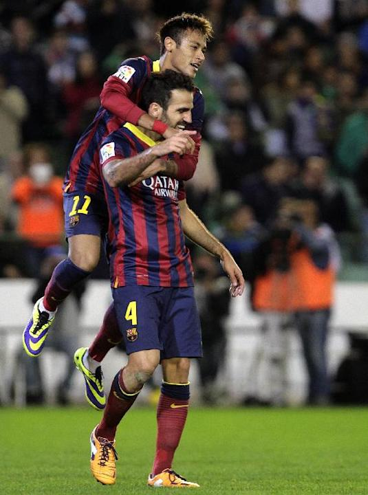 Barcelona's Francesc Fabregas, bottom, celebrates with teammates Neymar after scoring against Betis during their La Liga soccer match at the Benito Villamarin stadium, in Seville, Spain on Sunday, Nov