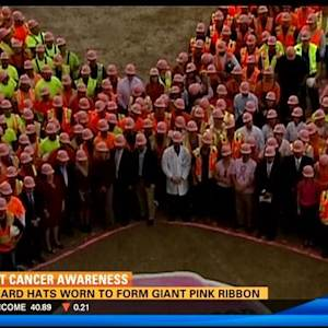 Pink hard hats worn to form giant pink ribbon