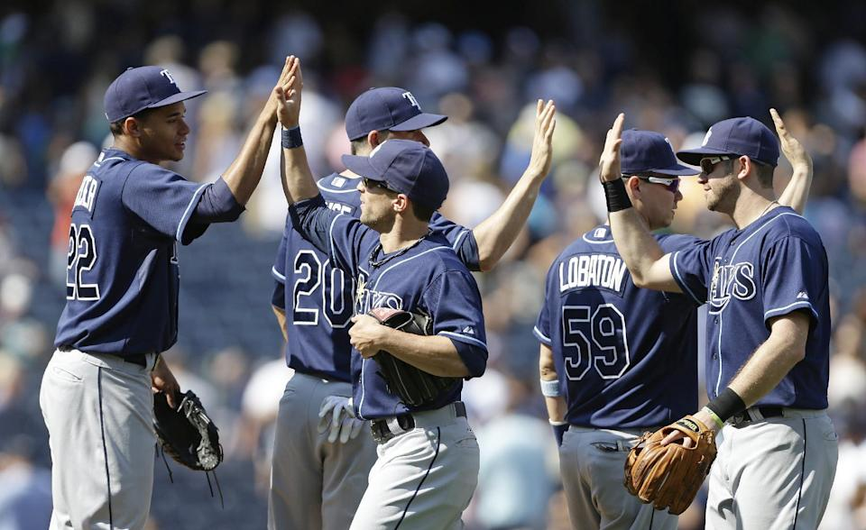 Tampa Bay Rays starting pitcher Chris Archer (22), Matt Joyce (20), and Jose Lobaton (59) celebrate with teammates after their 1-0 win over the New York Yankees in a baseball game Saturday, July 27, 2013, in New York. (AP Photo/Frank Franklin II)