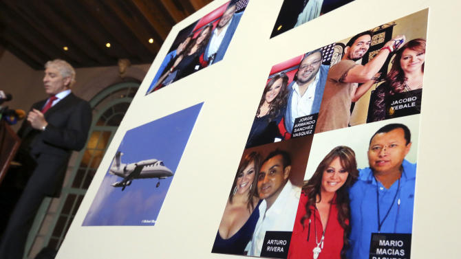 A poster showing pictures of Jenni Rivera with four of her associates, all killed in a plane crash in Mexico in December, is displayed during a news conference where attorney Paul Kiesel, left, announces a lawsuit on behalf of the four associates, in Los Angeles Thursday, Jan. 10, 2013. (AP Photo/Reed Saxon)