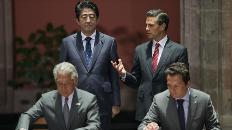 Mexico's President Enrique Pena Nieto, back right, and Japanese Prime Minister Shinzo Abe, back left, talk as bilateral cooperation agreements are signed by representatives of the two countries, at the National Palace in Mexico City, Friday, July 25, 2014. Abe was on an official visit to Mexico. (AP Photo/Rebecca Blackwell)