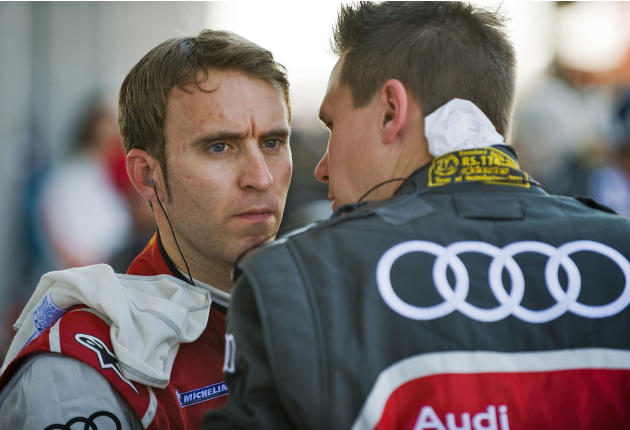Audi Sport Team Joest's Timo Bernhard, left, of Germany, talks with a team member on pit row during the annual American Le Mans Series 12 Hours of Sebring auto race at the Sebring International Racewa