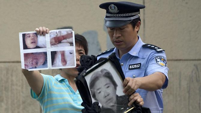 A woman holds up photos to attract public attention for her case as a policeman grabs the photos to stop her outside a hospital where Chinese activist Chen Guangcheng is staying for treatment in Beijing, China, Thursday, May 10, 2012. Authorities are tightening restrictions on the extended family of the blind activist whose flight from house arrest in rural China into the protection of the U.S. Embassy in Beijing set off a diplomatic dispute. (AP Photo/Alexander F. Yuan)