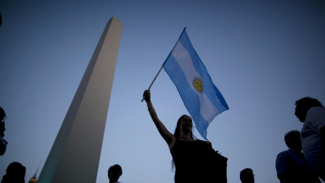 A woman waves an Argentina flag during an anti-government demonstration in Buenos Aires, Argentina, Thursday, Nov. 8, 2012. Thousands of people marched against rising inflation, crime, exchange controls and to express their fear to a constitutional reform that could open the way for a third consecutive reelection of Argentina's President Cristina Fernandez. (AP Photo/Natacha Pisarenko)