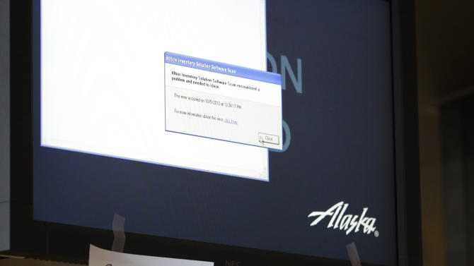 Hand-written Alaska Airlines flight numbers and destinations is shown taped to a check-in station computer monitor with an error message, Monday, Oct. 8, 2012, at Seattle-Tacoma International Airport in Seattle during a system-wide outage of the computers the airline uses to check in passengers. The airline was able to check in customers manually for a few flights, but most others were delayed or cancelled. (AP Photo/Ted S. Warren)