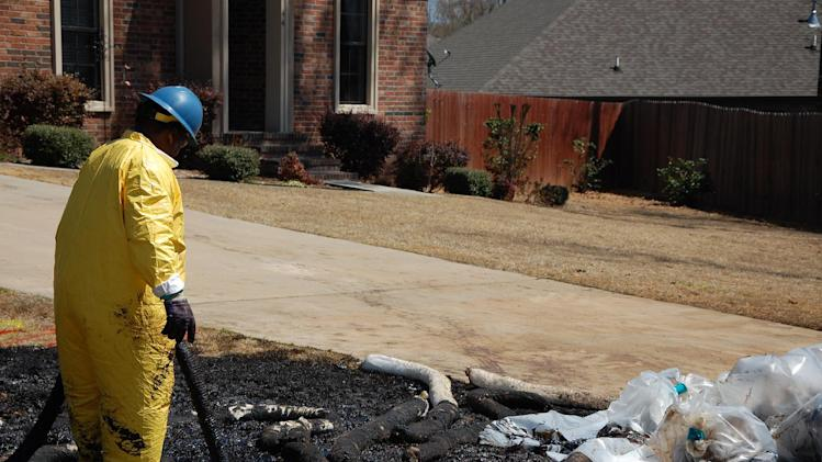 A worker cleans up oil in Mayflower, Ark., on Monday, April 1, 2013, days after a pipeline ruptured and spewed oil over lawns and roadways. (AP Photo/Jeannie Nuss)