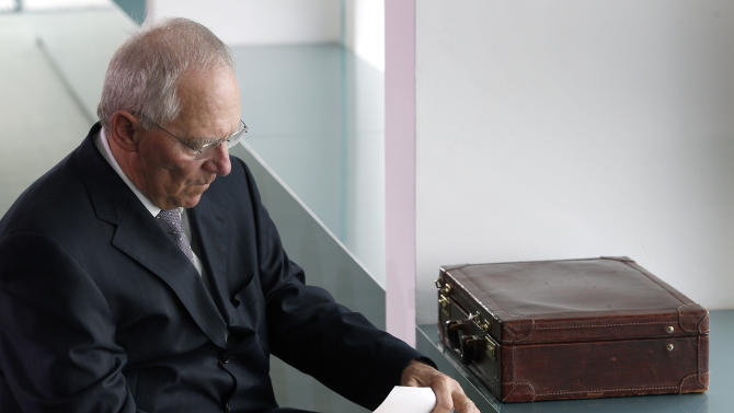 German Finance Minister Wolfgang Schaeuble sorts files at the beginning of the weekly cabinet meeting at the chancellery in Berlin, Germany, Wednesday, May 8, 2013. (AP Photo/Michael Sohn)