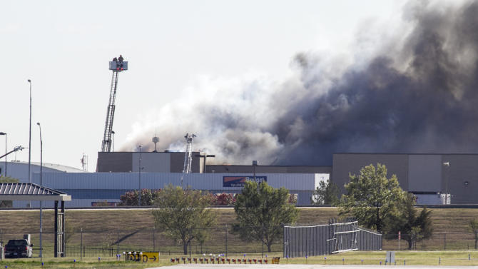 Firefighters try to put out a fire at Mid-Continent Airport in Wichita, Kan., Thursday. Oct. 30, 2014, shortly after a small plane crashed into the building killing several people including the pilot. (AP Photo/The Wichita Eagle, Mike Hutmacher)