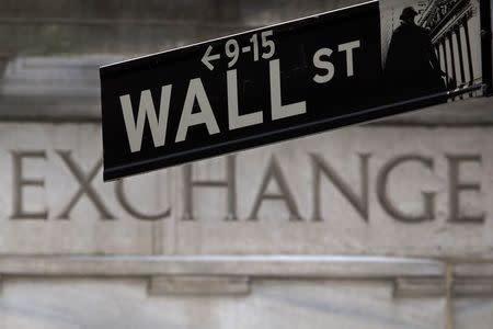 A Wall Street sign is pictured in front of the New York Stock Exchange, open during Winter Storm Juno, in the Manhattan borough of New York