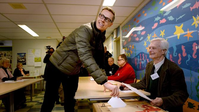Finnish Prime Minister and leader of National Coalition Party Alexander Stubb, front left, casts his vote in Espoo, Finland on Sunday April 19, 2015. Finns are voting in parliamentary elections that will determine which coalition of parties can lead the country out of a three-year recession. (Mikko Stig/Lehtikuva via AP) FINLAND OUT, NO SALES