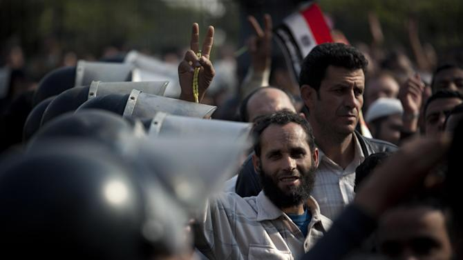"A Supporter of Egyptian President Mohammed Morsi flashes the Victory sign, as riot police gurad the entrance of Egypt's top court, in Cairo, Egypt, Sunday, Dec. 2, 2012. Egypt's top court announced on Sunday the suspension of its work indefinitely to protest ""psychological and physical pressures,"" saying its judges could not enter its Nile-side building because of the Islamist president's supporters gathered outside. (AP Photo/Nasser Nasser)"
