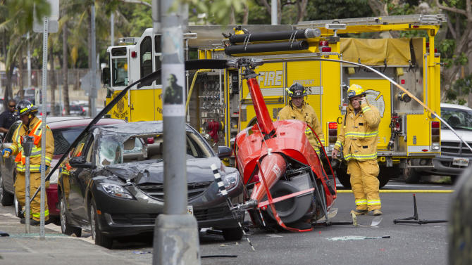 Honolulu firefighters look over the wreckage of a small helicopter that crashed next to a car near the intersection of Fort Street and Beretania Street in downtown Honolulu Wednesday, May 8, 2013. (AP Photo/Eugene Tanner)