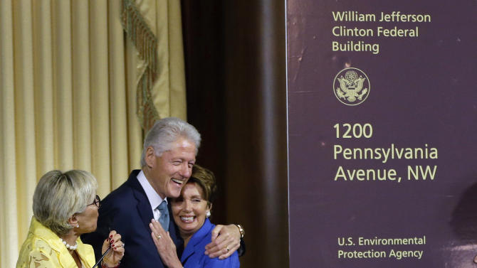 Former President Bill Clinton reacts and hugs House Minority Leader Nancy Pelosi of California as Sen. Barbara Boxer, D-Cailf., watches at left, during the ceremony naming the new Environmental Protection Agency headquarters for President Bill Clinton Wednesday, July 17, 2013, in Washington. (AP Photo/Pablo Martinez Monsivais)