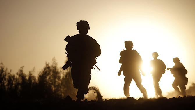 FILE - U.S. Marines with the 3rd Platoon, Bravo Company, 1st Battalion 5th Marines, run for cover as the Taliban approach, in the Nawa district, Helmand province, southern Afghanistan, Friday, Oct. 2, 2009. (AP Photo/Brennan Linsley, File)