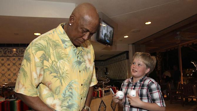 IMAGE DISTRIBUTED FOR WGN AMERICA - Chicago Cubs legend Fergie Jenkins, left, signs an autograph for James Padden-Rubin during the WGN America Spring Training Weekend Welcome Reception at the Phoenician Resort in Scottsdale, AZ. on Thursday, March 21, 2013.  (Rick Scuteri/AP Images for WGN America)