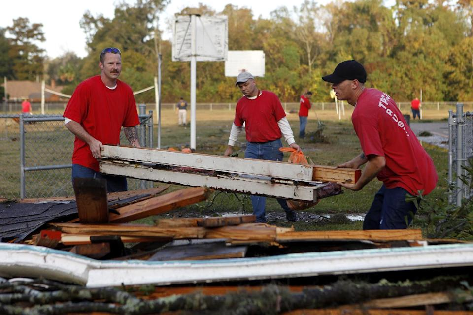 Terrebonne Parish trustees clean up storm debris left by strong winds from a suspected tornado Wednesday, Nov. 16, 2011 at Village East School in Houma, La. (AP Photo/The Houma Courier, Julia Rendleman)