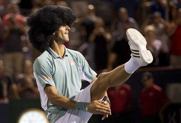Novak Djokovic, from Serbia, dances while wearing a wig as he celebrates his victory over Denis Istomin, from Uzbekistan, during third-round play at the Rogers Cup men's tennis tournament on Thursday,