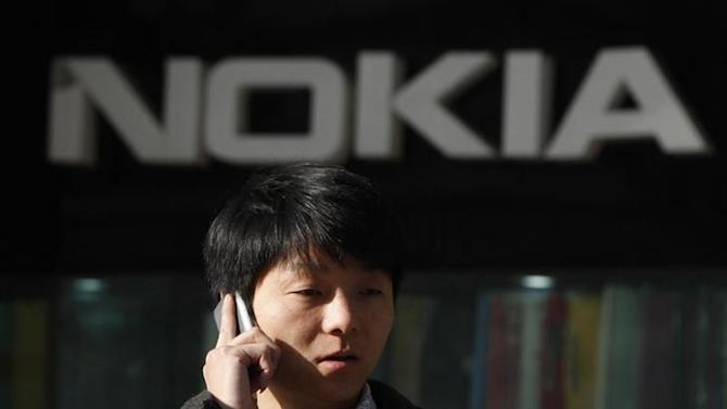 A man using his mobile phone walks under a Nokia logo in Shanghai December 6, 2012. REUTERS/Aly Song/Files