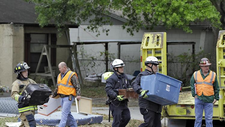 Hillsborough County, Fla., firefighters remove salvaged items, from the home where a sinkhole swallowed Jeffrey Bush, late Thursday in Seffner, Fla., on Sunday, March 3, 2013. Crews are set to begin the demolition of the home on Sunday, after search personnel failed to find Bush. (AP Photo/Chris O'Meara)