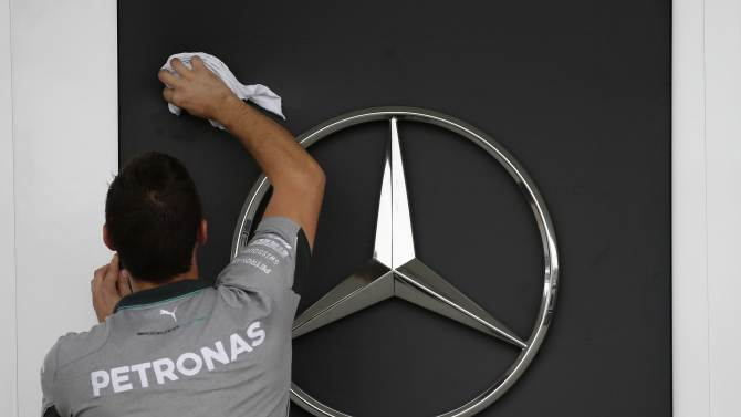 A Mercedes Formula One crew member cleans their team logo as they set up the garage at the Suzuka circuit in Suzuka