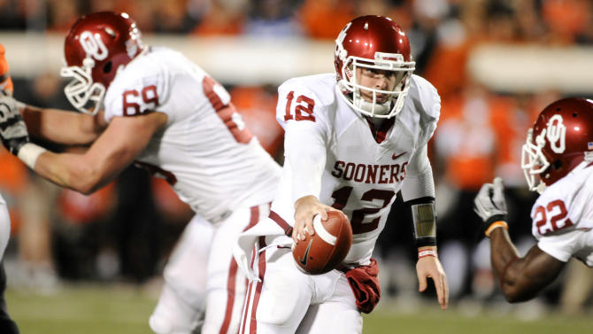 Oklahoma's Offensive Lineman Lane Johnson, left, blocks as quarterback Laundry Jones, center, fakes a hand-off to running back Roy Finch, right, during the first quarter of an NCAA college football game against Oklahoma State in Stillwater, Okla., Saturday, Dec. 3, 2011. (AP Photo/Brody Schmidt)