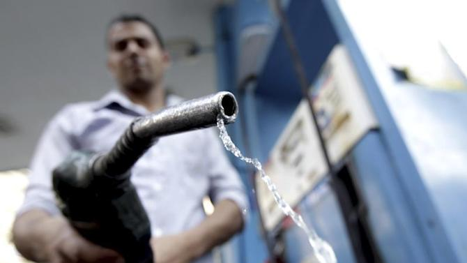 A worker holds up a fuel pump nozzle after filling up the tank of a car at a petrol station in Cairo