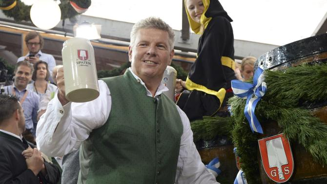 Newly elected mayor of Munich Reiter holds up a beer after tapping the first barrel during opening ceremony for 181st Oktoberfest in Munich