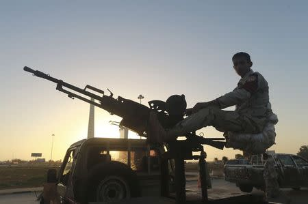 A Libyan military personnel mans a checkpoint in the city center in Benghazi