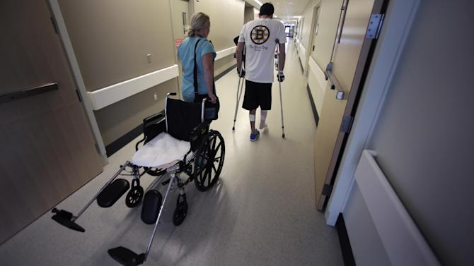 """In this Wednesday, May 22, 2013 photo, Boston Marathon bombing survivor Pete DiMartino, of Rochester, N.Y., is followed by his physical therapist Julia Broyer as he finishes a physical therapy session at the Spaulding Rehabilitation Hospital in Boston. DiMartino was injured in an explosion near the finish line, which blew away much of one leg and burned the other. """"I don't want anybody feeling sorry for me,"""" he said. """"... I want people to see that this has made me a better person and I want people to become better people through what they see through me."""" (AP Photo/Charles Krupa)"""