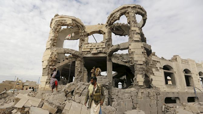 Houthi militants guard the house of Ali Haidar, a Houthi leader, destroyed by a Saudi-led air strike in Sanaa