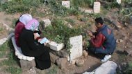Syrians mourn the death of a relative at a grave in the city of Rastan, just north of the central resitive city of Homs