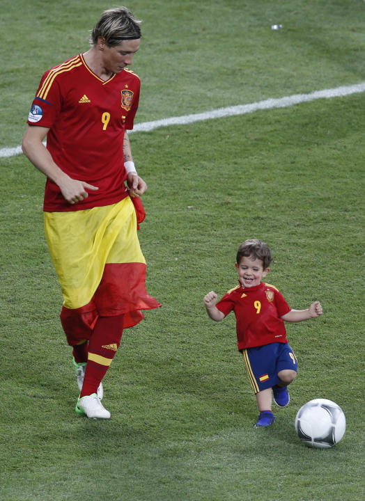 Spain's Torres plays ball with his son Leo after defeating Italy to win Euro 2012 final soccer match at Olympic stadium in Kiev