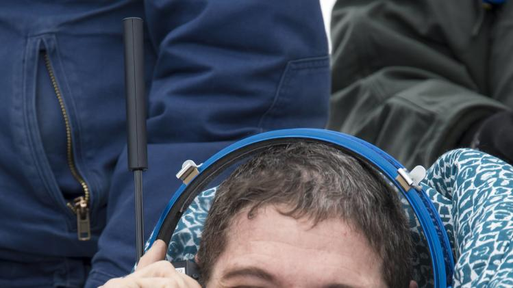 Astronaut Hopkins from NASA talks to his family via a satellite phone as he sits in a chair outside the Soyuz TMA-10M capsule shortly after the landing in a remote area southeast of Zhezkazgan