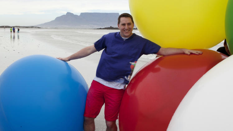 In this photo provided by Positivedialogue Communications on Tuesday, April 2, 2013, Matt Silver-Vallance poses with balloons against a backdrop of Table Mountain, in Cape Town, South Africa, Sunday, March 31, 2013.  Wind speed and direction permitting, Silver-Vallance will strap himself to 200 big balloons filled with helium, float off the island beneath a bulging latex column of color, and drift to the shores of Cape Town for a charitable cause. (AP Photo/Trevor Wilkins)