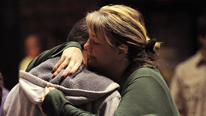 Oakdale, Minn., resident Amy Berger hugs an unidentified young man at a candlelight vigil for nine year-old Devin Aryal at Holy Cross Lutheran Church in Oakdale, Tuesday night, Feb. 12, 2013.  Berger's son went to daycare with the slain child. (AP Photo/Pioneer Press, Chris Polydoroff)