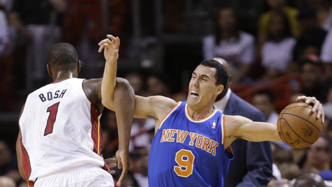 New York Knicks guard Pablo Prigioni (9) is fouled by Miami Heat center Chris Bosh (1) during the first half of an NBA basketball game, Tuesday, April 2, 2013 in Miami. (AP Photo/Wilfredo Lee)