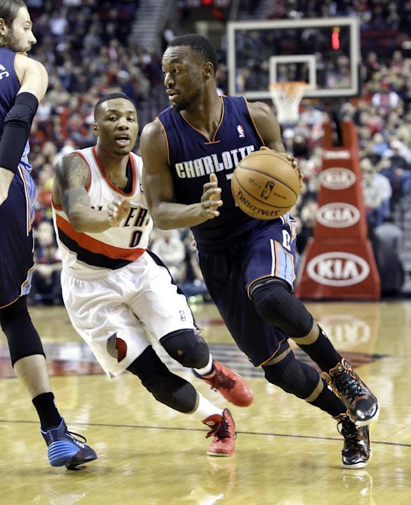 Charlotte Bobcats guard Kemba Walker, right, drives past Portland Trails Blazers guard Damian Lillard during the first half of an NBA basketball game in Portland, Ore., Thursday, Jan. 2, 2014. (AP Pho