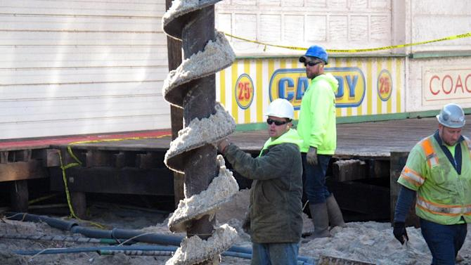 A worker positions a drill on the sand in Seaside Heights N.J. on Friday, Feb. 15, 2013 as the town began building its iconic boardwalk that was destroyed in Superstorm Sandy.  Mayor Bill Akers says the mile-long walkway should be done by May 10, but amenities like railings, lighting and ramps will come after that. (AP Photo/Wayne Parry)
