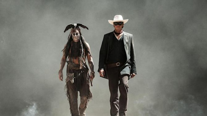 """FILE - This undated file photo provided by Disney and Jerry Bruckheimer, Inc. shows Johnny Depp, left, as Tonto, and Armie Hammer as The Lone Ranger, in a scene from the film """"The Lone Ranger."""" Domestic box office numbers so far on this long Fourth of July holiday weekend are suggesting the highly anticipated, $250 million Western extravaganza is in serious danger of becoming the train wreck of the summer movie season. The animated minions of family favorite """"Despicable Me 2,"""" with a price tag one third of what """"The Lone Ranger"""" cost to make, is outperforming the masked man by more than three to one. (AP Photo/Disney/Jerry Bruckheimer, Inc., Peter Mountain, File)"""