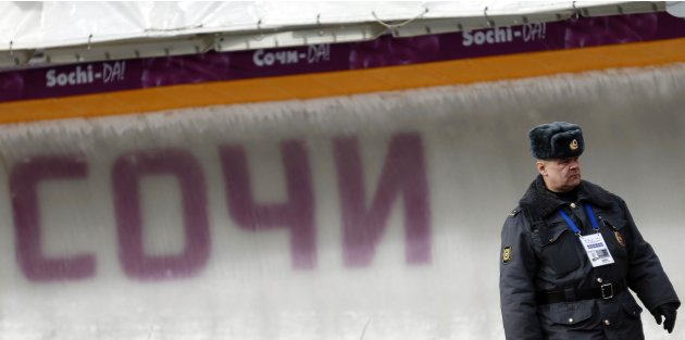 "A Russian police man walks next to the track during the women's luge World Cup at the ""Sanki"" sliding center in the winter sport resort of Rosa Khutor, a venue for the Sochi 2014 Winter Olympics near"