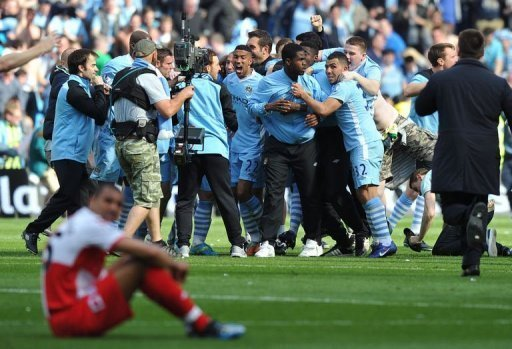 Manchester City's players and supporters celebrate on the pitch after their 3-2 victory
