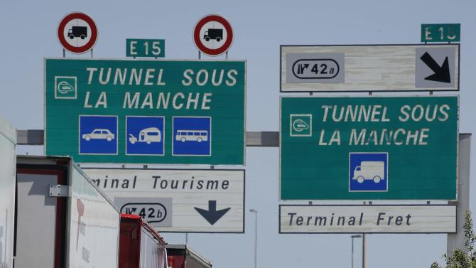 Truck drivers wait near their lorries blocked on a road which leads to the Channel Tunnel terminal in Coquelles near Calais, northern France