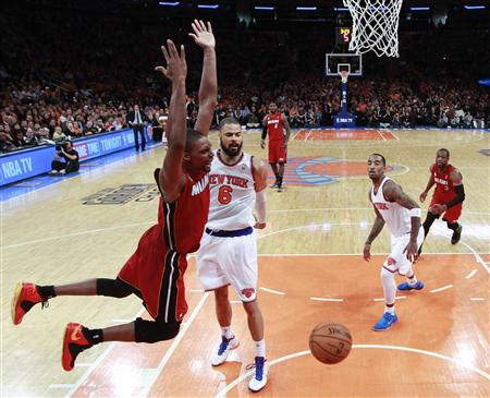 Miami Heat's Bosh reacts after scoring against New York Knicks' Chandler and Smith in their NBA basketball game in New York