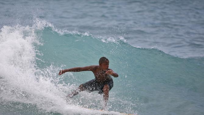 A boy surfs a wave at a beach in Barahona, Dominican Republic, before the anticipated arrival of Tropical Storm Isaac, Thursday, Aug. 23, 2012. U.S. forecasters said Isaac will likely turn into a Category 1 hurricane by Friday as it nears the Dominican Republic and Haiti. (AP Photo/Ricardo Arduengo)