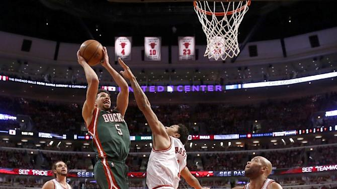 Milwaukee Bucks guard Michael Carter-Williams (5) scores over Chicago Bulls guard Derrick Rose (1) as Joakim Noah (13) and Taj Gibson (22) watch during the second half in Game 5 of the NBA basketball playoffs Monday, April 27, 2015, in Chicago. The Bucks won 94-88. (AP Photo/Charles Rex Arbogast)